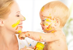 cheerful happy dirty baby draws paints on her face of mother
