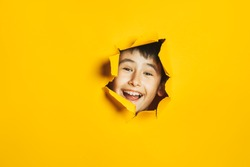 Cheerful happy face of child looking into hole in torn yellow paper wall. Sidebar for text, promotional information, advertising, positive news, events, sale, discount, best choice.