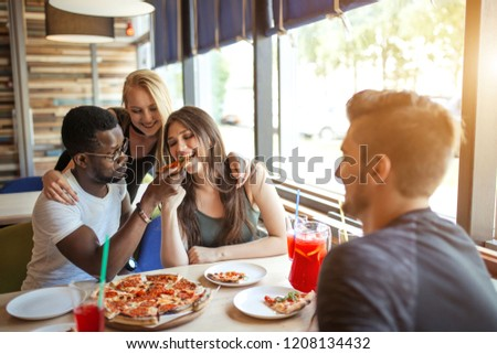 Cheerful happy male and female students treating each other with organic pizza with different toppings and non alchoholic cocktails, having fun and enjoying meal and carefree talks.