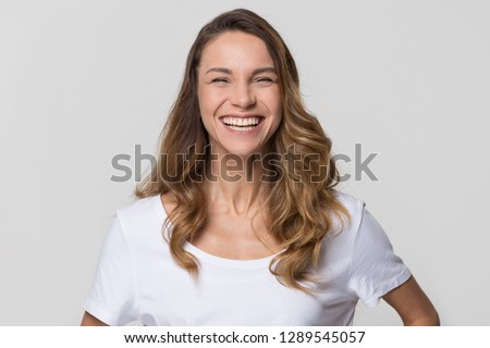 Cheerful happy millennial woman laughing looking at camera isolated on white studio blank background, smiling funny young girl having fun, portrait, healthy teeth dental care, orthodontic service