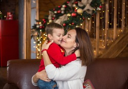 Cheerful happy mom and little son 4 years old on background of wooden house beautifully decorated before Christmas hug each other.  Cozy Christmas atmosphere