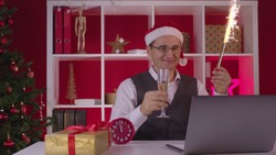 Cheerful happy 40s corporate employee in Santa hat participates in Online Christmas party with laptop drinking champagne holding firework fountain Celebrate event remotely