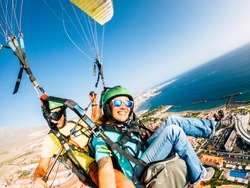 Cheerful happy woman to paraglyde experience with pilot - couple having fun in the air paraglyding over the city with coastline view - tourist and summer holiday vacation active people