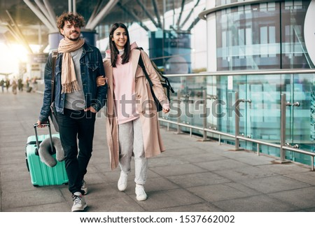 Cheerful happy young couple walk together outside of airport. Guy carry suitcase. She hold his hand. Travel together. Trip or vacation. Sunlight outside. Walking together