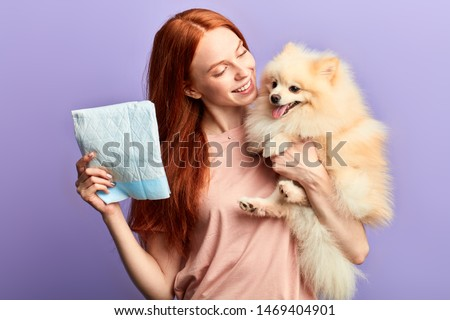Cheerful happy young woman looking after pretty dog like a baby. close up portrait, isolated blue background, studio shot. lifestyle, spare time, free time