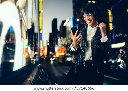 Cheerful hipster girl choosing song from mobile playlist enjoying nightlife in New York,happy trendy woman in spectacles reading message on smartphone listening music on street with neon illumination