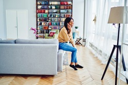 Cheerful hipster girl in casual clothing enjoying cellular conversation during weekend in cozy living room, happy African American woman calling to friend for talking and recreating in home