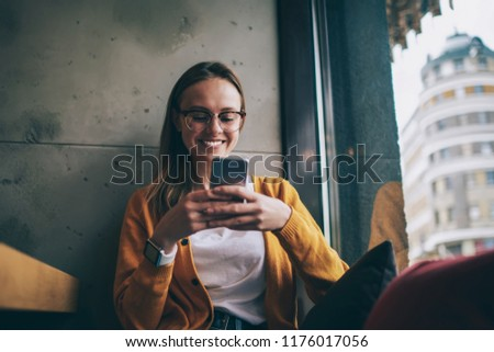 Cheerful hipster girl in eyeglasses feeling excited of chatting with friends using free 4g internet on cellular phone, happy female blogger watching video via media app on telephone during spare time