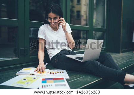 Cheerful hipster girl in optical eyewear enjoying smartphone communication with best friend during time for e learning and preparation to college exams, happy Spanish student with laptop phoning