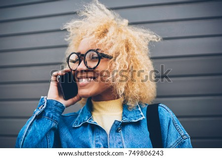 Cheerful hipster girl in trendy spectacles having mobile conversation with friend enjoying free time,happy young woman satisfied with connection and cheap tariffs for calls having phone conversation