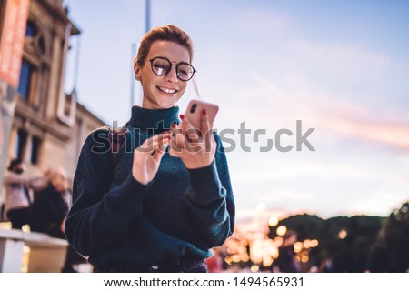 Cheerful hipster girl reading pleasant text message from best friend connected to public internet outdoors, happy woman with beautiful smile chatting on cell smartphone while relaxing outdoors