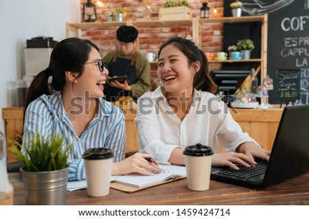 Cheerful hipster girls coworkers in shirt laughing while having positive conversation. two freelancer colleagues using laptop computer at cafe table. blurred view male waiter in counter making coffee