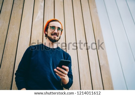 Cheerful hipster guy in spectacles connecting his smartphone to 4G internet in roaming, smiling caucasian man in trendy wear using mobile phone for chatting outdoors satisfied with technology