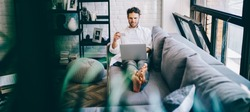 Cheerful hipster guy lying on sofa in modern designed living room making online shopping via laptop computer and wifi, man holding credit card paying for purchases in web store rest at home