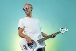 Cheerful hipster man play white bass guitar in neon lights. Rock music concept. Rock star.