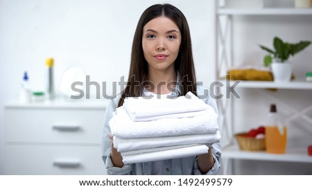 Cheerful housekeeper holding clean towels, laundry service for busy people #1492499579