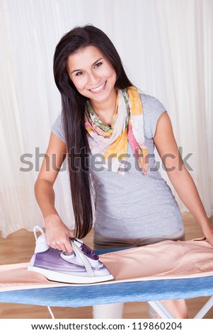 Cheerful housewife with a beautiful smile standing at the ironing board ironing clothes against a white curtained window with copyspace
