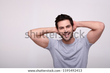 Cheerful, in a cool mood a young stylish handsome man with brown hair and brown eyes, in a gray T-shirt, threw his hands behind his head and a cute smiling looks at the camera. Copy space. Copy space.
