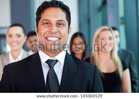 cheerful indian businessman with colleagues on background