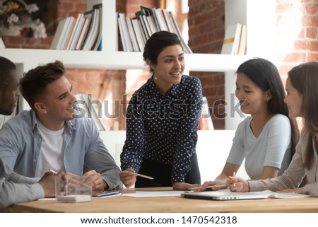 Cheerful indian female team leader involved in studying process, explaining new material to mixed race friends. Group of smiling diverse students discussing together school project ideas in classroom.