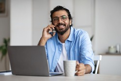 Cheerful Indian Freelancer Guy Drinking Coffee And Talking On Cellphone While Having Break During Work With Laptop Computer At Home Office, Speaking With Friends, Resting At Workplace, Free Space