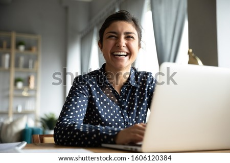 Photo of Cheerful indian girl student professional laughing looking away sit with laptop computer at home office table, positive hindu woman having fun enjoy sincere emotion laughter studying working on pc