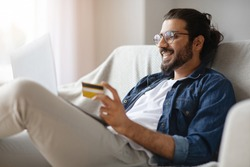Cheerful Indian Guy In Eyeglasses Using Laptop And Credit Card At Home For Online Payments, Sitting On Comfortable Couch, Transferring Money, Shopping In Internet Or Booking Vacation, Free Space
