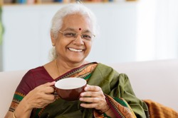 Cheerful Indian lady holding a big cup and looking at the camera