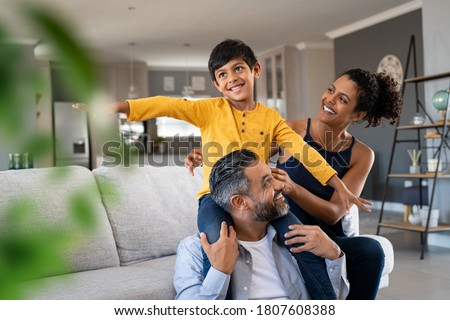Cheerful indian son sitting on father shoulder playing at home with african mother. Playful little boy enjoying spending time with parents at home. Flying child enjoying playing with his ethnic family