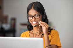 Cheerful indian woman in smart working from home. Happy middle eastern girl working as customer service representative with laptop. Smiling young woman with headset doing video call at home.