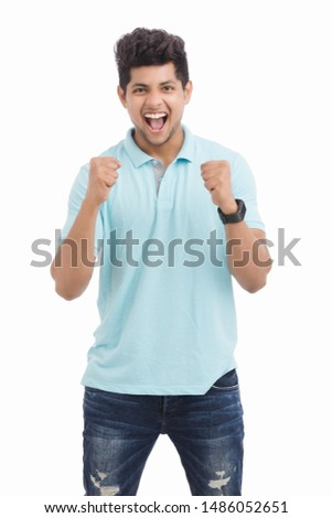 Cheerful Indian young man cheering after won