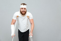 Cheerful injured young man walking with crutches over white background