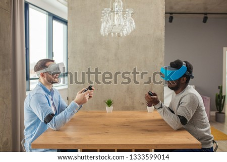 Cheerful interracial male gamers having fun with new trends technology, sitting against each other at table with virtual reality headset on .