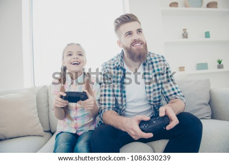 Cheerful joyful excited stylish trendy father and daughter holding joy-sticks in hands playing video game sitting on couch indoor in living room enjoying free time wearing casual outfit front view #1086330239