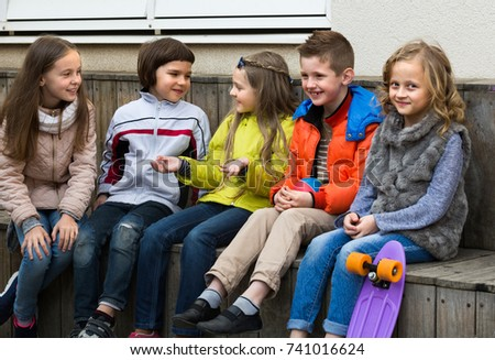 Cheerful junior kids chatting and having fun outdoor in city street