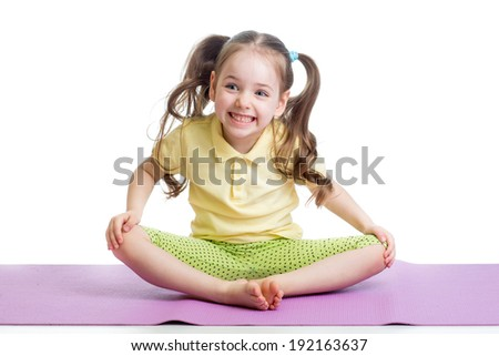 Cheerful kid girl doing exercises on fitness mat