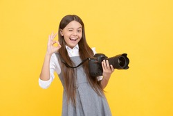 cheerful kid girl take photo with digicam show ok gesture, photography.
