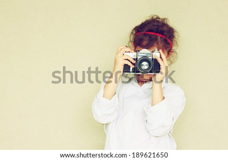 Cheerful kid holding old camera. retro filter room for text.