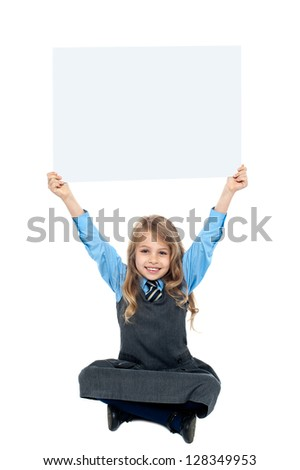 Cheerful kid sitting on floor and holding ad board above her head.