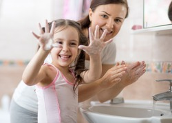 Cheerful kid washing hands and showing soapy palms