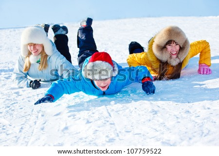 Cheerful kids and their mother sliding down the snowy hill