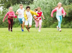 Cheerful kids are jogging together in the park and having fun
