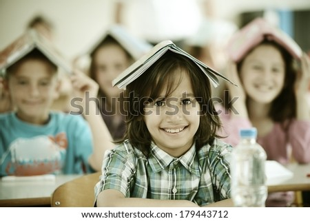 Cheerful kids at school room having education activity with books