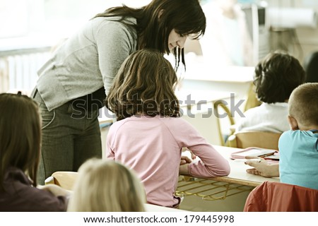 Cheerful kids at school room having education activity with teacher