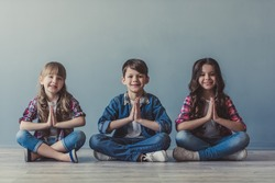 Cheerful kids in casual clothes are looking at camera and smiling while sitting in lotus positions on the floor