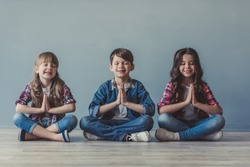 Cheerful kids in casual clothes are smiling while sitting in lotus positions on the floor
