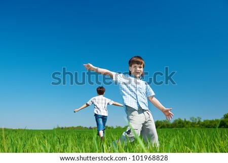 Cheerful kids running in the field