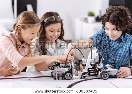 Cheerful kids working on the tech project at school