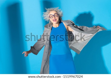 Cheerful lady. Cheerful fashionable curly woman wearing blue dress and grey trench coat #1519967024