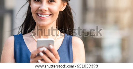 Cheerful lady inscribing sms by mobile #651059398